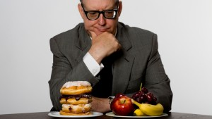 Man contemplating eating healthy or unhealthy food, studio shot