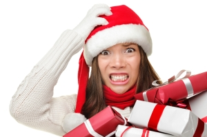 Christmas stress - busy woman wearing santa hat stressing for christmas shopping holding may christmas gifts in her arms. Funny image of multiracial Asian Caucasian female model isolated on white background.