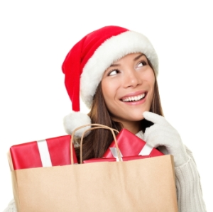 Christmas shopping woman thinking wearing santa hat and holding christmas gifts in shopping bag. Thinking mixed race Chinese Asian / Caucasian female model looking sideways smiling happy isolated on white background.
